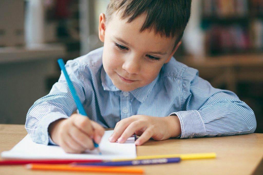 Little boy writing at school