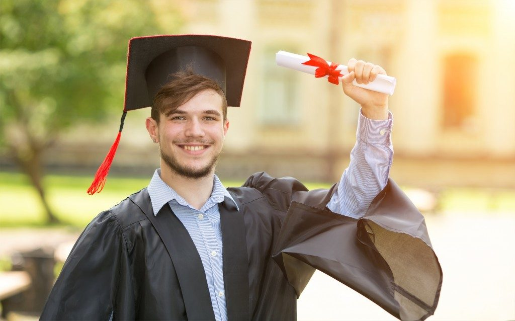 A student happily received his diploma on his graduation