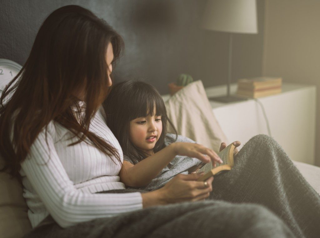 mom reading her daughter a bedtime story