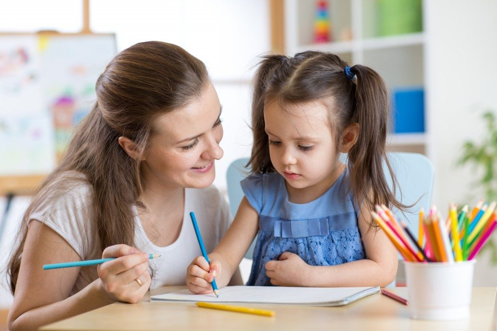 a mother joining her daughter in learning how to write
