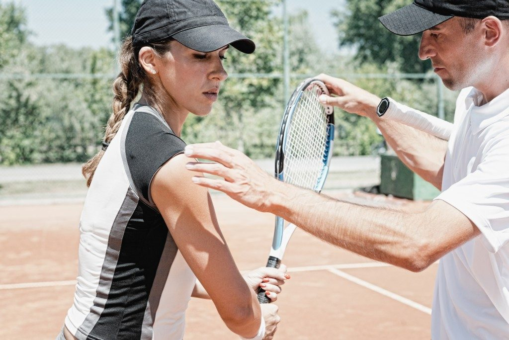 coach teaching his tennis player the right positioning