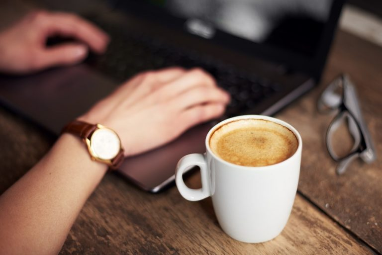 close up photo of hands typing in a laptop with a coffee at the side