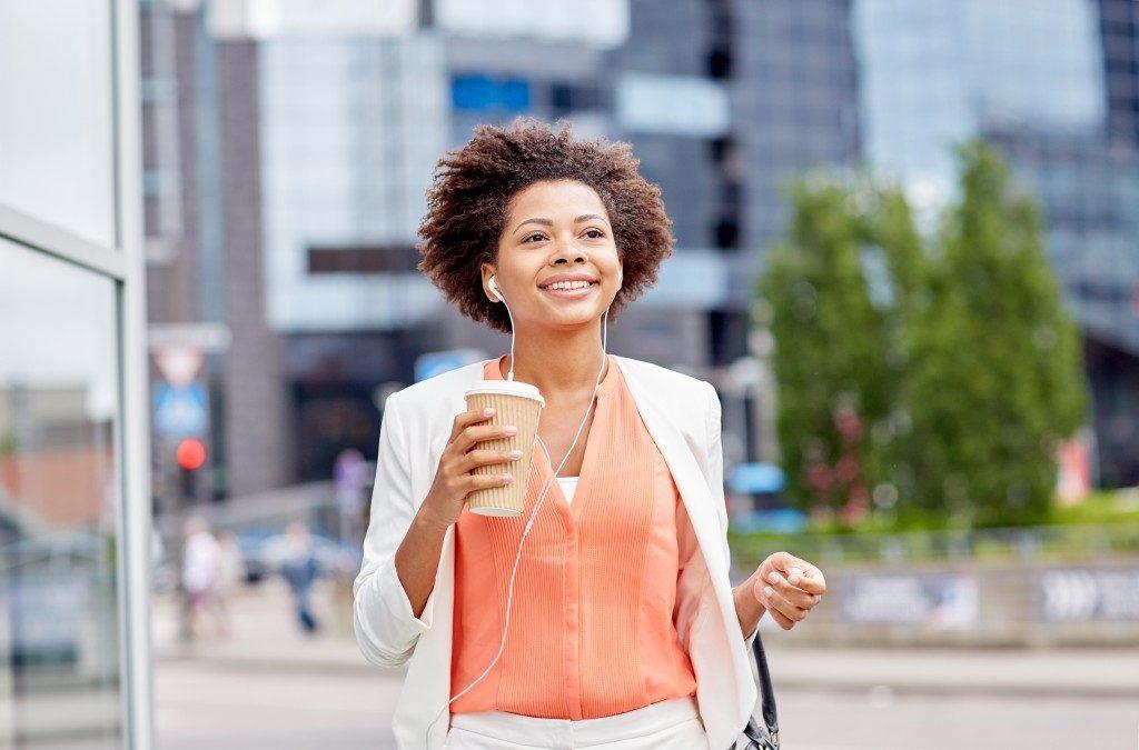 Happy businesswoman holding coffee