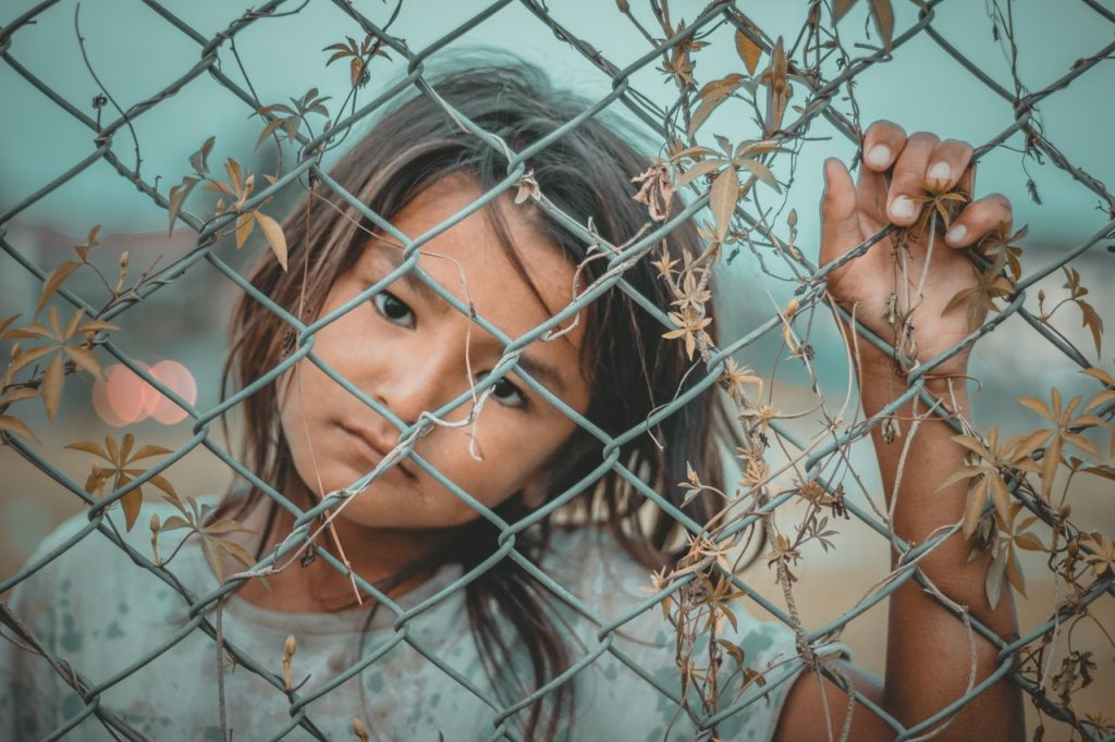 young child holding on to steel fence